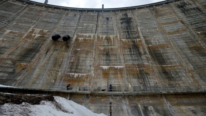 Dam operator Paul Bergstrom and his dog Jake make their way to the gatehouse at Gibson Dam, which stands 195 feet tall.