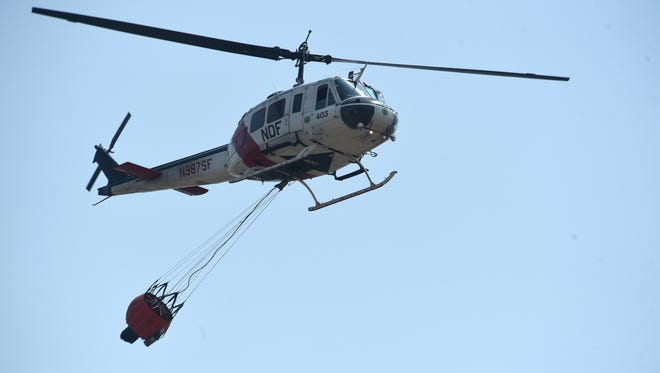 A Nevada Division of Forestry helicopter hurries to pick up some more water while fighting the Perry Fire in the Palomino Valley area north of Reno on July 31, 2018.