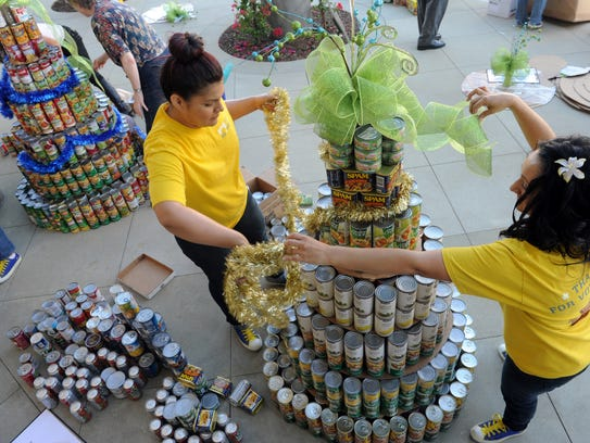 Volunteers put the finishing touches on a tree made of cans of food in 2012.