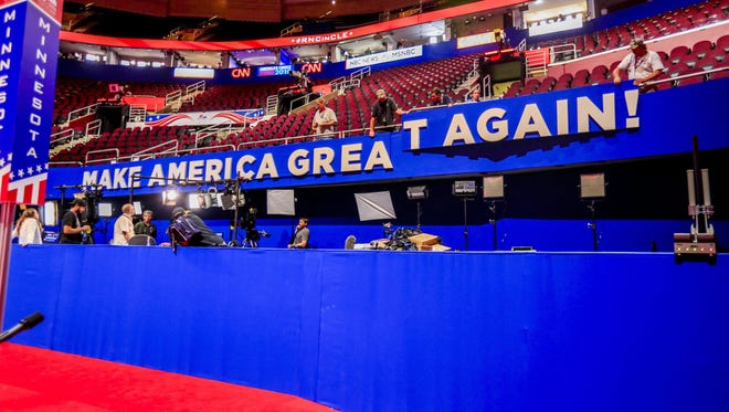 Workers hang a sign with the Trump campaign slogan at the Quicken Loans Arena in Cleveland ahead of the Republican National Convention.
