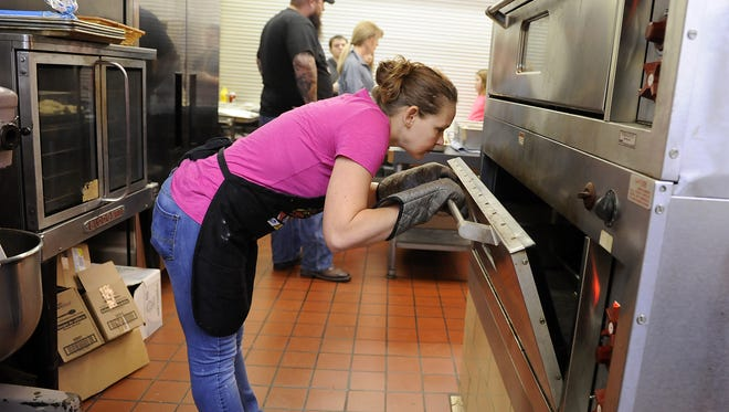 Volunteer April Hartings peeks in the oven to check on the stuffing as Nick Curry organizes the serving line before the start of the annual Curry family Christmas dinner in 2015. Curry's grandfather, Homer, started hosting the free meal in the 1950s.