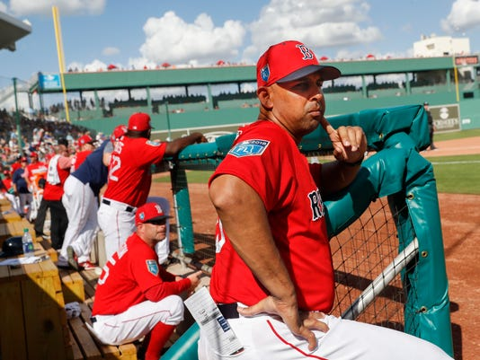 FILE - In this Feb. 24, 2018, file photo, Boston Red Sox manager Alex Cora stands in the dugout in the fourth inning of the team's spring training baseball game against the Tampa Bay Rays in Fort Myers, Fla. Rookie manager Cora has been given the keys to a baseball Cadillac. His only directives – as with any new driver -- don't crack it up and don't bring it back on empty. (AP Photo/John Minchillo, File)