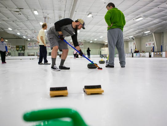 Brian Hufe sweeps the curling stone towards the end