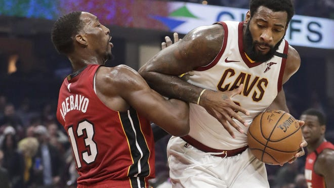 FILE - Cleveland Cavaliers' Andre Drummond, right, drives past Miami Heat's Bam Adebayo in the first half of an NBA basketball game,  in Cleveland.  On Friday, March 6, Drummond, Cavs guards Collin Sexton and Darius Garland, forwards Cedi Osman, Dante Exum and Dylan Windler, coach J.B. Bickerstaff, his entire staff and general manager Koby Altman, spent several hours visiting with offenders at Grafton _ a medium security prison housing 1,700 residents to share fellowship as well as some hope and hoops.