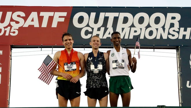 First placed Galen Rupp, center, stands on the platform flanked by second-placed Benjamin True, left, and third-placed Hassan Mead, right, after the 10,000 meters event at the U.S. Track and Field Championships in Eugene, Ore., Thursday, June 25, 2015.