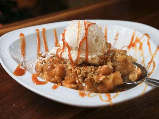 Village Anchor's Huber's Winesap apple crisp includes bourbon-apple cider aramel, with Comfy Cow vanilla bean idea cream and Bourbon Barrel sea salt. Chef is Kyle Fields.