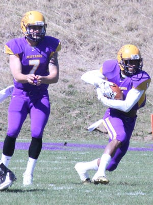 Western quarterback Mitch Glasmann hands the ball off to Marques Rodgers.