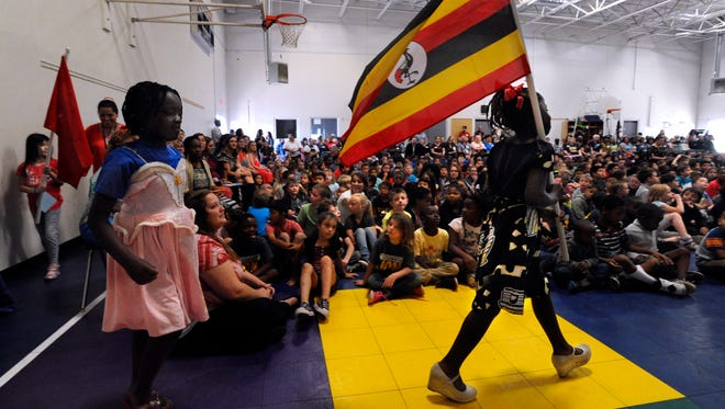 Third-grader Winner Moligi carries the flag of Uganda Thursday, May 18, 2017, at Lee Elementary School. Students from 19 countries carried the flags of the nations from which their families came during an assembly celebrating the school's international diversity.