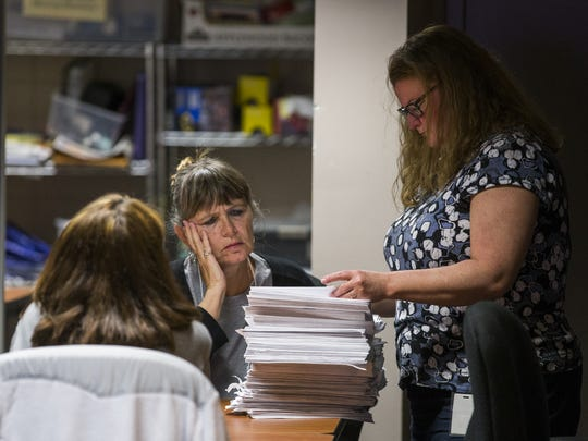 Johanna Stiles, center, and Dana McBride, right, prepare to open one of several stacks of vote-by-mail ballots to present to the Leon County, Florida Canvassing Board on Nov. 8, 2016 in Tallahassee, Fla.