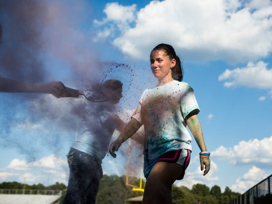 Laura Griffin of Pendleton is sprayed with pigmented powder during a color run fundraiser for School District 4 on Thursday, September 15, 2016 in Pendleton.