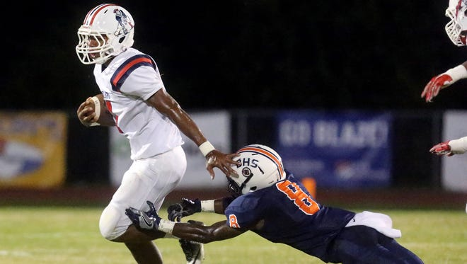 Oakland's Lazarius Patterson (4) runs the ball as Blackman's Jamis Carson (8) misses a tacke during the game on Friday, Sept. 16, 2016, at Blackman.