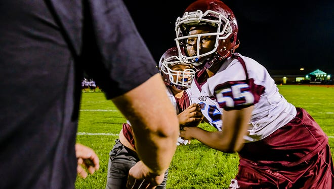 Okemos lineman Dayon Williams ,right, fights through a block by a teammate during their first practice of the new football season at midnight Monday August  7, 2017 in Okemos.  KEVIN W. FOWLER PHOTO
