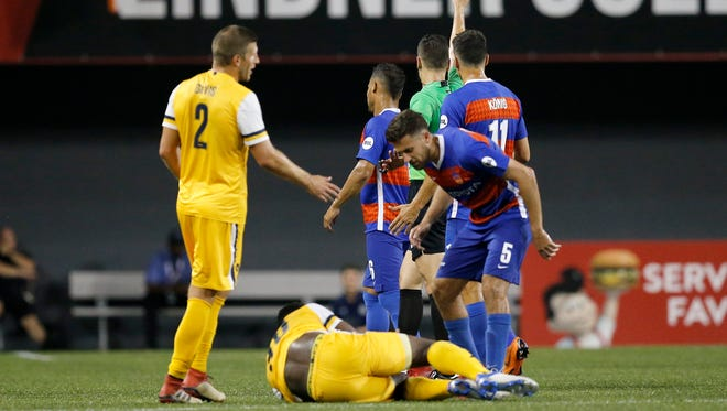 FC Cincinnati midfielder Kenney Walker (6) receives a yellow card for a collision with Nashville SC midfielder Bolu Akinyode (30) in the second half of the USL soccer match between the FC Cincinnati and the Nashville SC at Nippert Stadium in Cincinnati on Saturday, Aug. 4, 2018. FC Cincinnati gave up a late goal and settled for a 1-1 tie against Nashville.