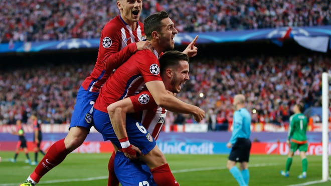 Atletico's Saul, bottom, celebrates with teammates Koke and Antoine Griezmann after scoring his side's opening goal during the Champions League 1st leg semifinal soccer match between Atletico Madrid and Bayern Munich at the Vicente Calderon stadium in Madrid, Spain, Wednesday, April 27, 2016. (AP Photo/Paul White)