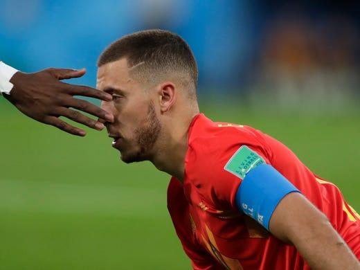 Belgium's Eden Hazard is helped stand up by France's