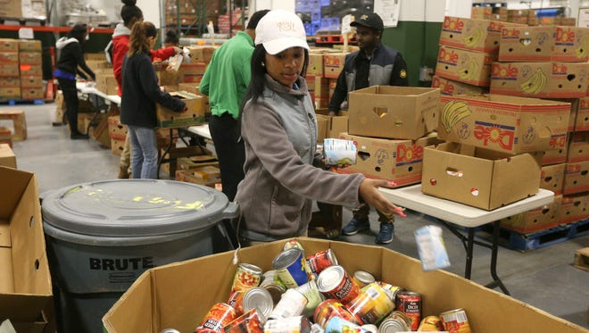 Kiki Coles, a Wegmans employee, drops cans of food into larger containers at Foodlink earlier this year.