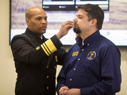 United States Surgeon General Vice Admiral Jerome Adams, demonstrates the use of Narcan on Jody Jaggers, director of Pharmacy Emergency Preparedness in Kentucky.  The event at the Northern Kentucky Health Department in Florence was an opportunity for Adams to talk about the importance of naloxone to reverse the effects of an opioid overdose. Most first responders already carry the medication, but Adams is encouraging family and friends of people who are at risk to carry naloxone.