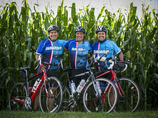 Marco Prada, center, and his sons Marco Prada, left, of Iowa City and Daniel Prada, right, of Las Vegas with cycling team Dublin Underground in Fort Dodge Monday July 20, 2015, during RAGBRAI XLIII.