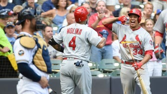 St. Louis Cardinals catcher Yadier Molina is greeted by shortstop Yairo Munoz after Molina hit a 2-run home run in the sixth inning against the Brewers at Miller Park.