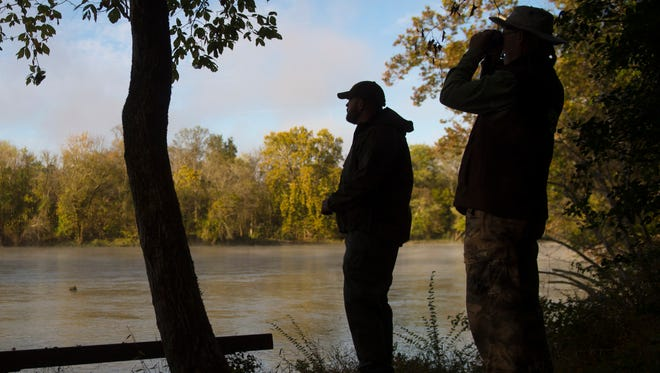 Ranger Tyler Farrar, left, and ornithologist Mark Armstrong watch for birds along the French Broad River on Monday, Oct. 20, 2014, at Seven Islands State Birding Park.