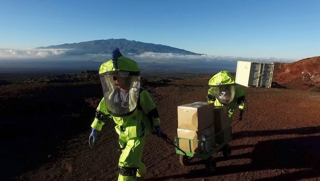 In this 2017 photo released by the University of Hawaii crew members of Mission V, walk up hill with a cart next to the university's facility Hawaii Space Exploration Analog and Simulation (HI-SEAS) at the Mauna Loa volcano, Big Island, Hawaii.