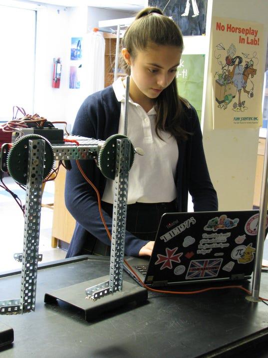 ASH ninth grader Lauren Pardi demonstrates use of one of the school's VEX ro.JPG