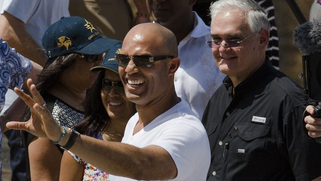 """Mariano Rivera waves to the crowd as Panama Canal Administrator Jorge Quijano, right, stands next to him during a visit to the Miraflores Locks at the Panama Canal in Panama City on Friday. The Yankees and the Miami Marlins will play Saturday and Sunday in the """"Legend Series"""" to honor the recently retired Yankees closer."""