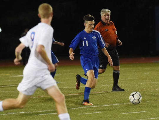 Millbrook's Dylan Madison, center, takes the ball down