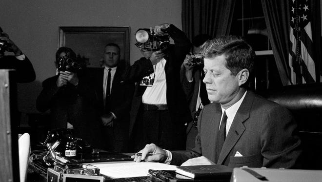 Secret Service agent Frank Yeager, seen center in front of the painting between the photographers, keeps a watchful eye as President John F. Kennedy signs the Interdiction of the Delivery of Offensive Weapons to Cuba in the Oval Office on Oct. 23, 1962. Yeager worked for Kennedy from 1961 to his assassination, later becoming a superintendent of schools for 29 years, including 7 years working for Owensboro, Ky. Public Schools.