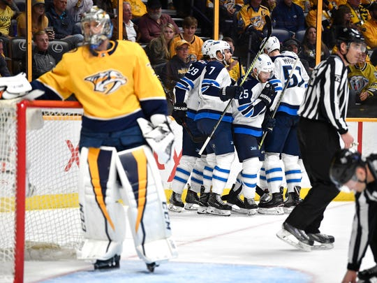The Jets celebrate as Predators goalie Pekka Rinne (35) looks away after giving up Winnipeg's second goal in game 1 of the second round NHL Stanley Cup Playoffs at the Bridgestone Arena Friday, April 27, 2018, in Nashville, Tenn.