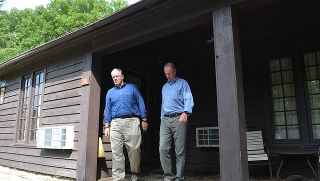 Gov. Jay Nixon and Parks Director Bill Bryan inspect a CCC-era cabin at Montauk State Park.