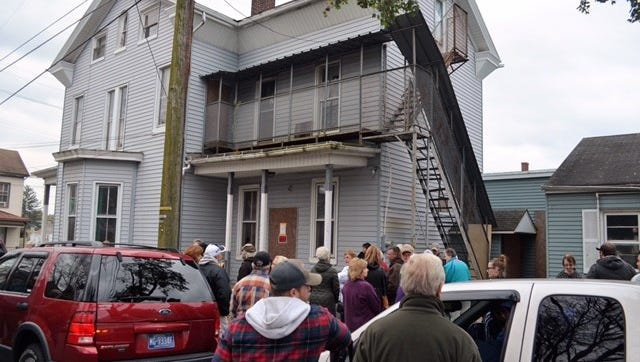 Part of the crowd attending the Coover Mansion auction on Wednesday, Nov. 1 awaits further word from Myerstown Borough officials on the level of bidding.