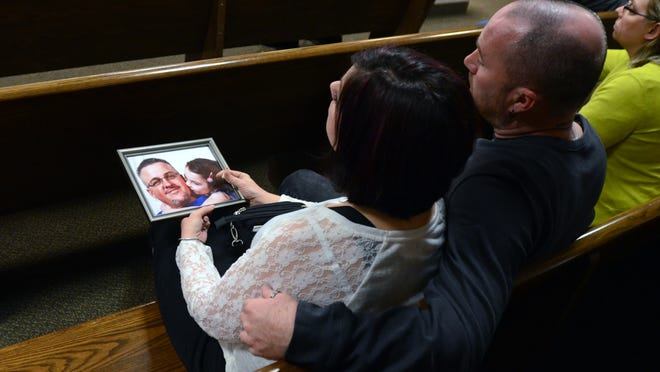 Family members of Timothy Tacie sit next to a photo of him and his daughter Monday, March 16, 2015 during the sentencing of Tommy Taylor Judge Lane's courtroom.