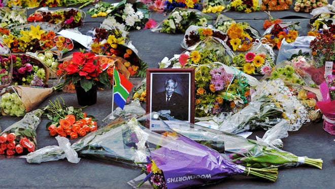 Flowers left by mourners surround a portrait of Nelson Mandela in the Sandton district of Johannesburg on Dec. 6, 2013.
