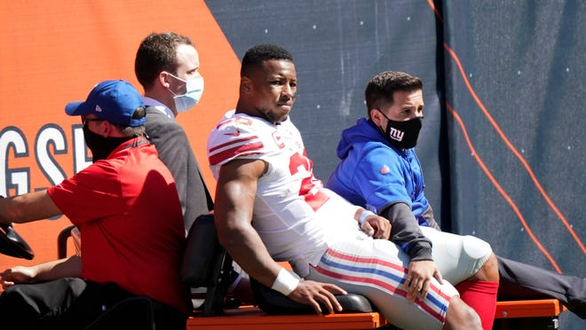 Giants running back Saquon Barkley is carted to the locker room after being injured during the first half Sunday in Chicago.