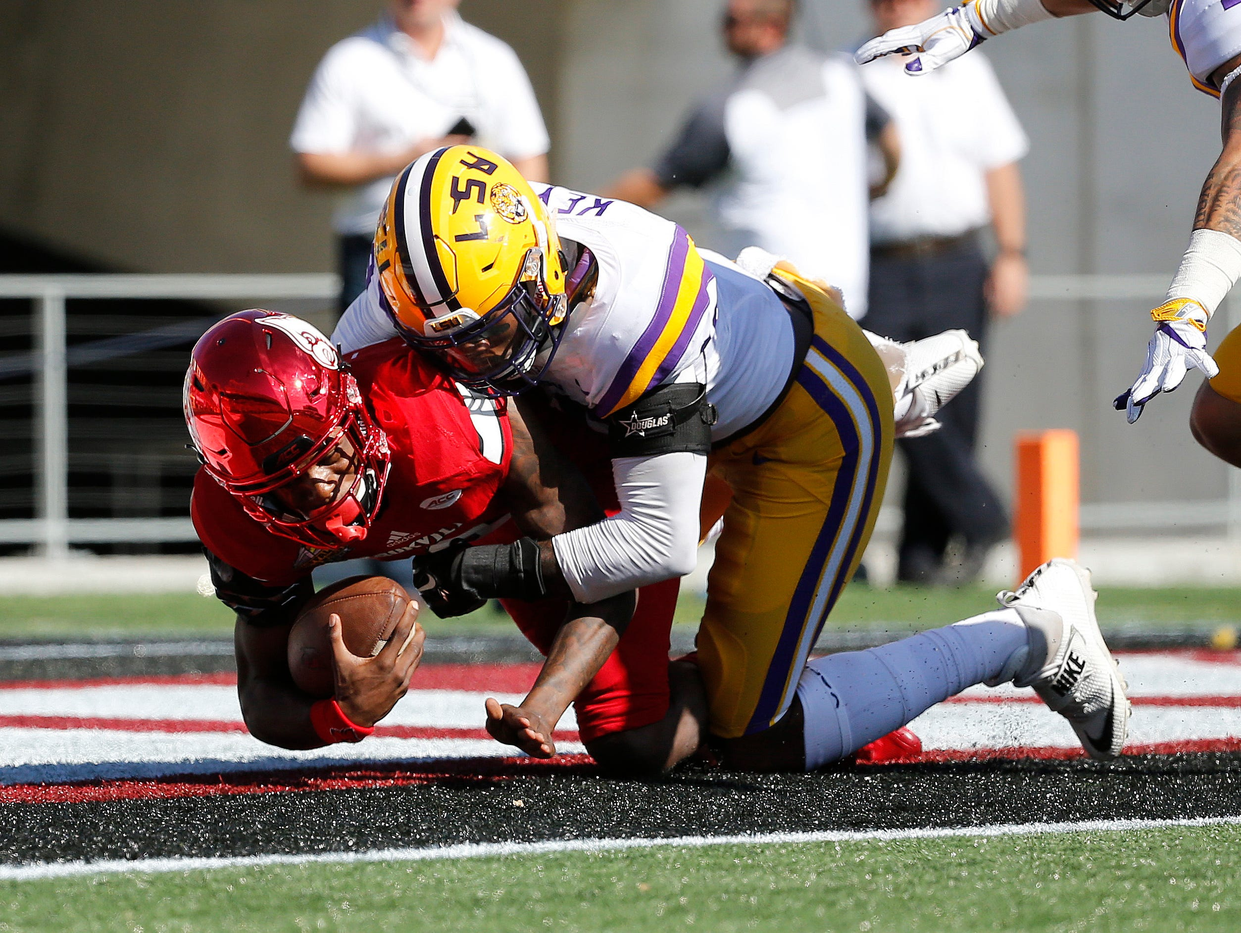 Louisville Cardinals quarterback Lamar Jackson (8) is sacked for a safety by LSU Tigers defensive end Arden Key (49) during the first half at Camping World Stadium.