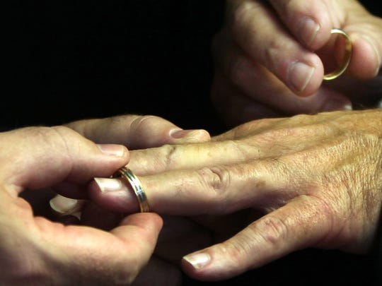 Terry L. Bond, Jr. places a wedding ring on the finger of his partner, Carl D. Fox, during their Kentucky wedding ceremony at Stephen L.J. Hoffman Wedding Chapel, Covington.   (they were married in New York three years ago but must obtain a Kentucky license for the marriage to be recognized in Kentucky.