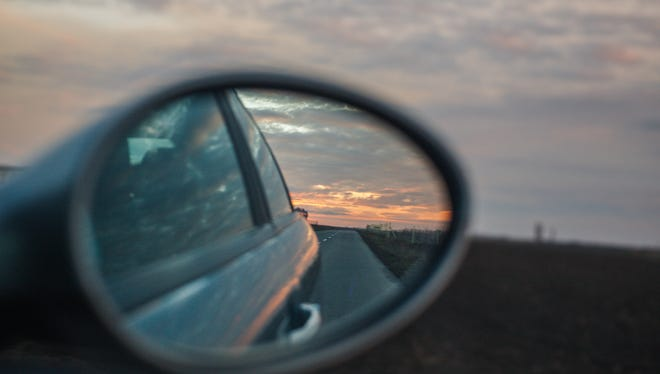 Sunset and road in a rear view mirror, no people