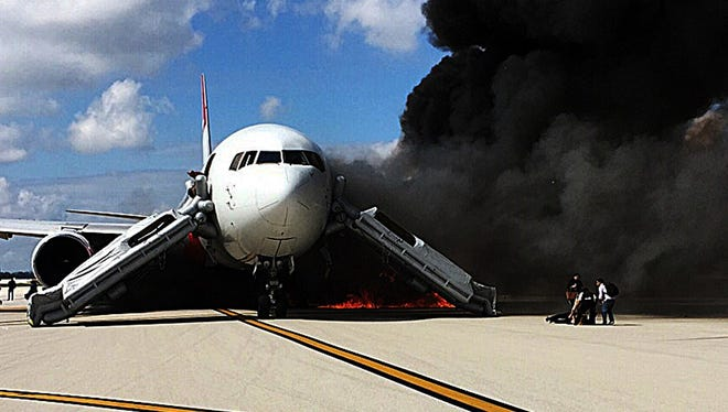 "Passengers evacuate from a plane on fire at Fort Lauderdale airport, in Fla. on October 29, 2015. An airliner caught fire on a runway and several people were injured, authorities said. ""Airplane engine fire,"" the Broward County Sheriff's Office said on Twitter, adding: ""several injuries."""