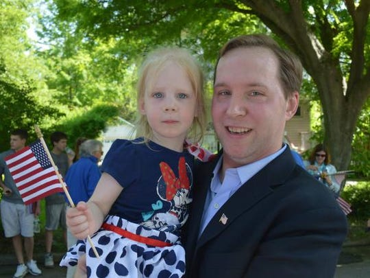 Attorney Justin Wagner, at the 2014 Chappaqua Memorial Day parade with his daughter, Samantha, is the Democratic nominee for the 40th Senate District. He wants a constitutional amendment to bar unfunded state mandates, which would be enforced by a new state bureaucracy.