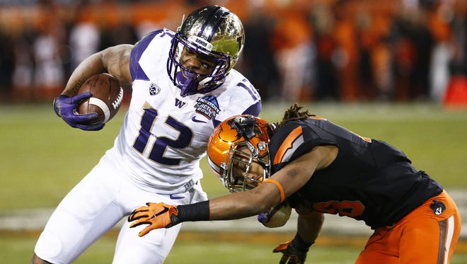 Washington's Dwayne Washington is stopped short on a 4th down play by Oklahoma State's Ramon Richards in the first half on Friday, Jan. 2, 2015 at the Ticket City Cactus Bowl in Tempe, AZ.
