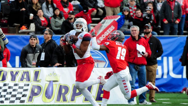 Arizona Wildcats wide receiver Cayleb Jones (1) matches a catch for a first down as New Mexico Lobos cornerback Nias Martin (19) defends during the first half in the 2015 New Mexico Bowl at University Stadium.