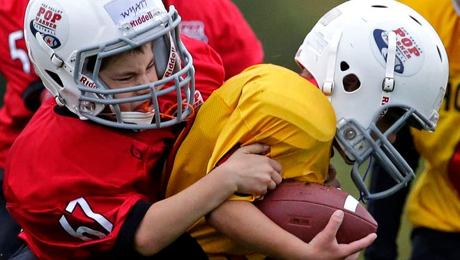 Wyatt Romenesko of the Force tackles AJ Pheifer of the Hornets in the Mitey-Mite division Fox Valley Pop Warner Football game in 2016.