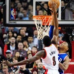 Portland Trail Blazers guard Damian Lillard (0) celebrates with teammate C.J. McCollum (3) after hitting a shot late in the fourth quarter of an NBA basketball game against the Philadelphia 76ers in Portland, Ore., Saturday, March 26, 2016. The Blazers won 108-105. (AP Photo/Steve Dykes)
