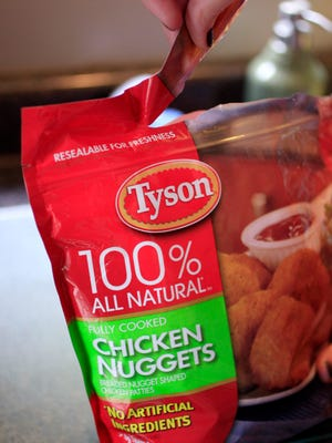 Jamey Boccio opens up a bag of frozen Tyson Chicken Nuggets at her home in Palo Alto, Calif., Sunday, May 8, 2011. (AP Photo/Paul Sakuma)