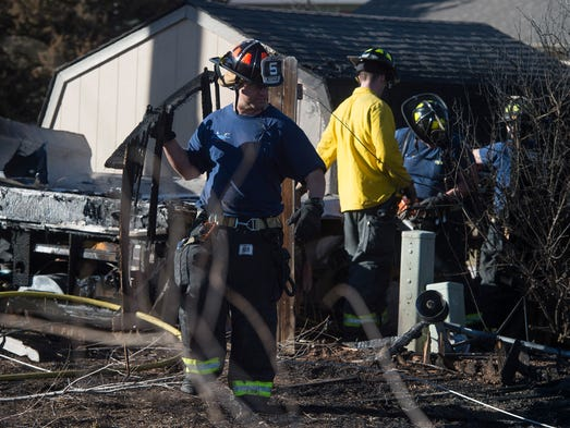 Crews work to clean up after a fire burned fences,