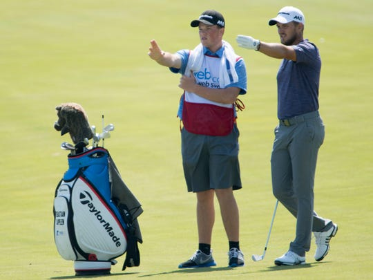 Sebastian Cappelen survies a shot with his caddie, Walker Beck, at the 18th hole during the 2018 United Leasing & Finance Championship.