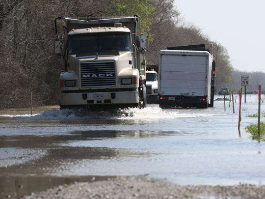 Trucks drive through a flooded area on Meadow Lark Lane, which leads to White Oaks Landfill, on Tuesday. White Oaks landfill is closed due to flooding.