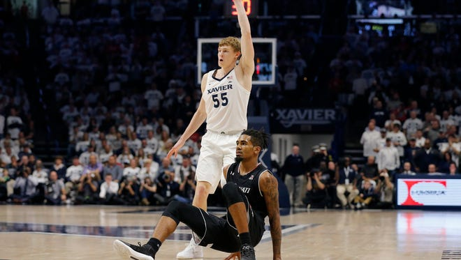 Xavier Musketeers guard J.P. Macura (55) calls for a pass after Cincinnati Bearcats guard Jacob Evans III (1) falls to the floor after a shot in the second half of the 85th Annual Crosstown Shootout game between the Xavier Musketeers and the Cincinnati Bearcats at the Cintas Center in Cincinnati on Saturday, Dec. 2, 2017. The Musketeers won't the annual crosstown rivalry game, 89-76, dealing UC its first loss of the season.