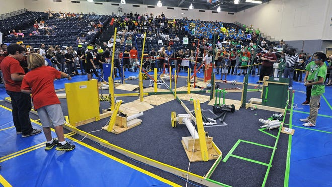 Students maneuver their robots around the course Saturday during the Emerald Coast BEST (Boosting Engineering, Science, and Technology) Robotics competition at the University of West Florida.